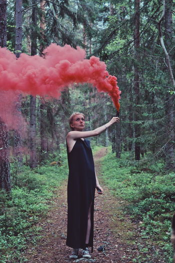 Woman With Red Smoke Flare In Forest