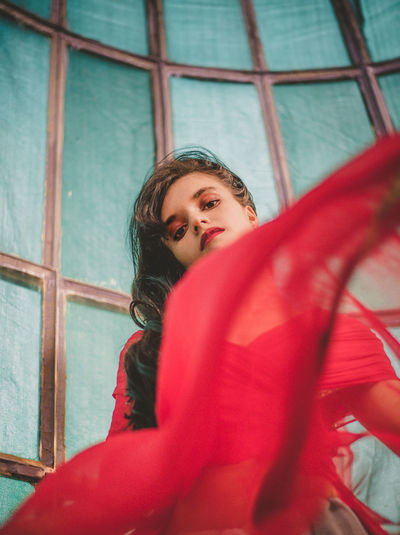 Low angle portrait of young woman wearing red dress against wall