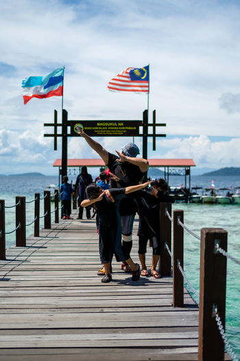 People on wooden bridge over sea against sky in bohey dulang.