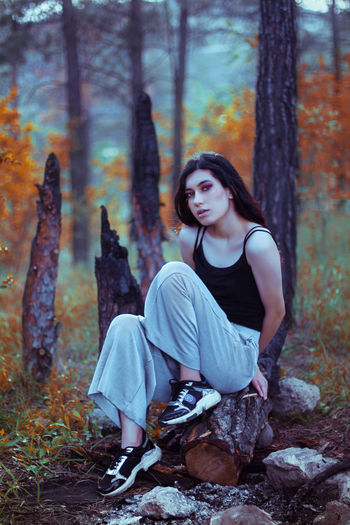 Portrait of woman sitting on rock in forest during autumn