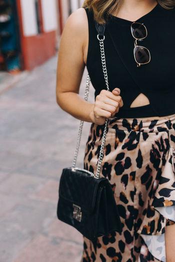 Midsection of woman holding a handbag
