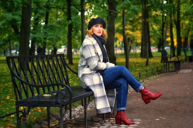 Portrait of beautiful young woman sitting on bench at park