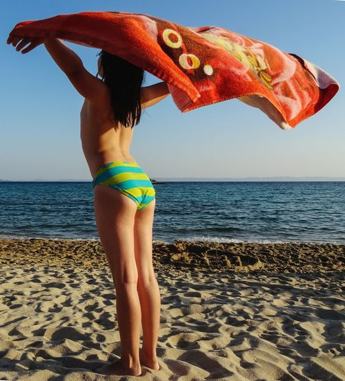 Rear View Of Girl Holding Beach Towel At Beach On Sunny Day
