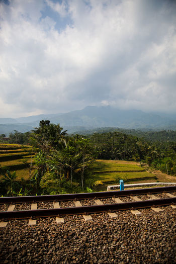 Cloudy Sky Public Transportation Railroad Track Rice Paddy Traveling Jungle Mountain Range In The Background Rural Scene Stacked Rings Tourism Train Across Java Indonesia View Out Of The Train Window
