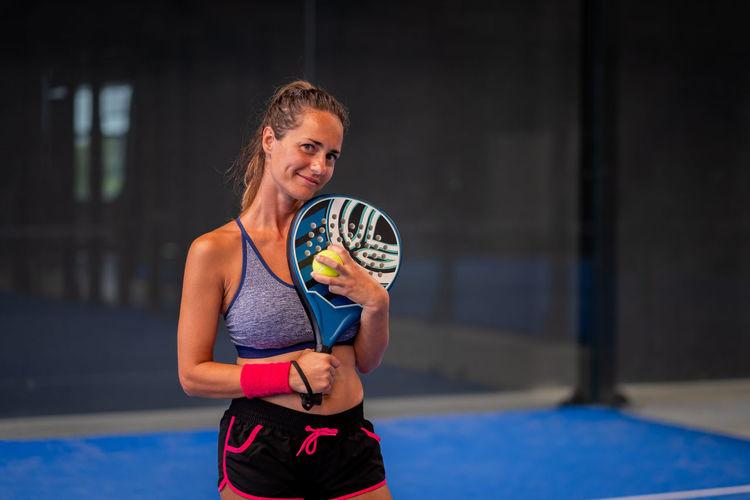 Portrait of beautiful woman playing padel tennis court indoor