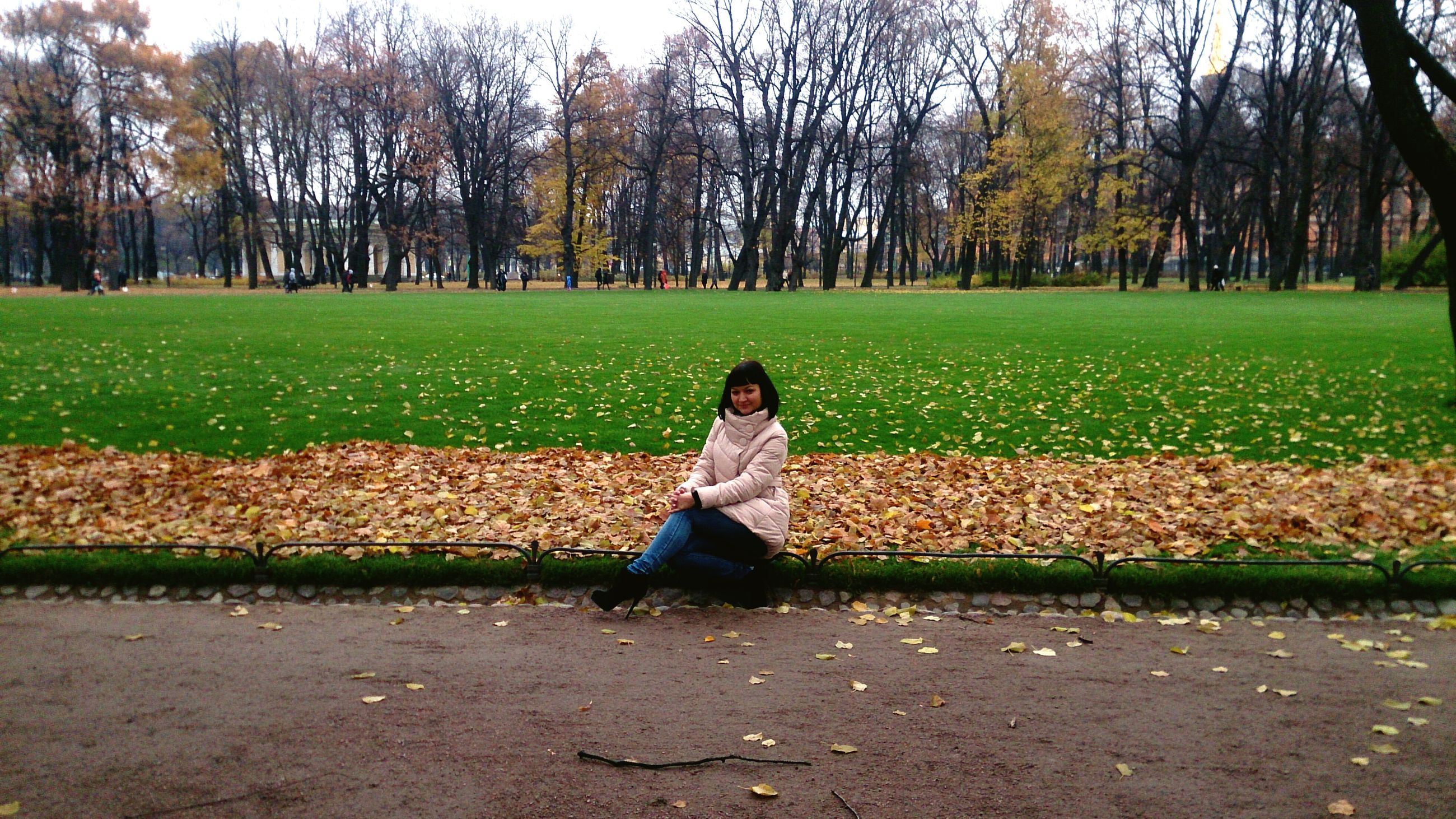 tree, lifestyles, leisure activity, casual clothing, grass, person, full length, young adult, field, park - man made space, sitting, standing, relaxation, young women, day, outdoors, park, tranquility
