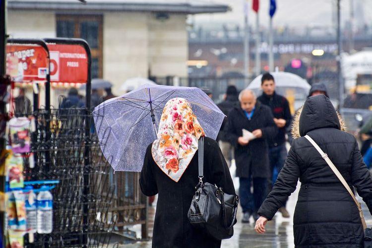 Rear view of people walking on street in rain