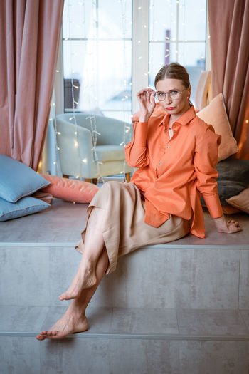 Woman in the studio sits on background of window in glasses and bright clothes
