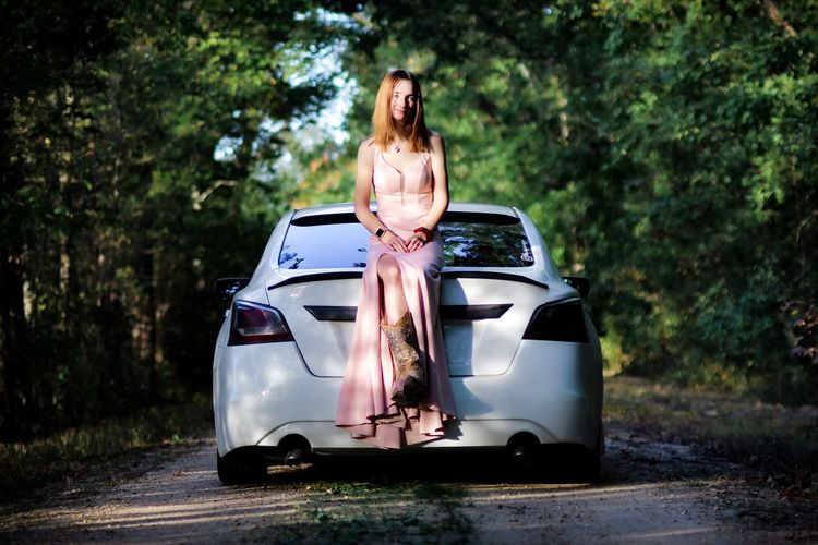 Full length of woman sitting on car amidst trees