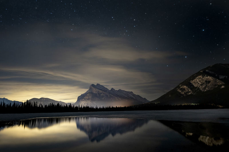 Rundle mountain reflected in vermillion lake at night