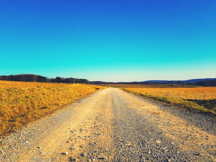 Dirt road amidst field against clear blue sky