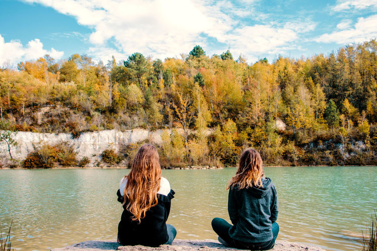 Rear view of two women sitting by lake against mountain
