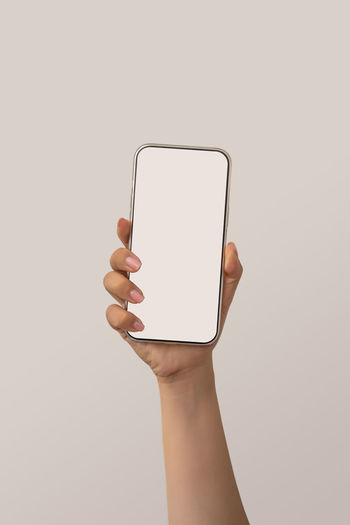 Person holding smart phone over white background