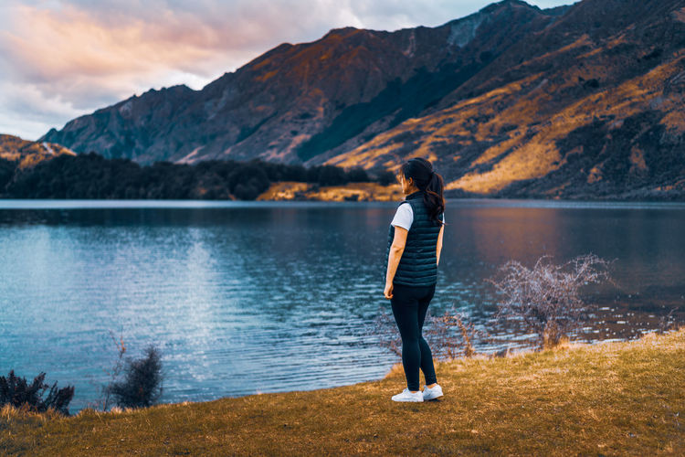 Rear view of woman standing by lake against mountains