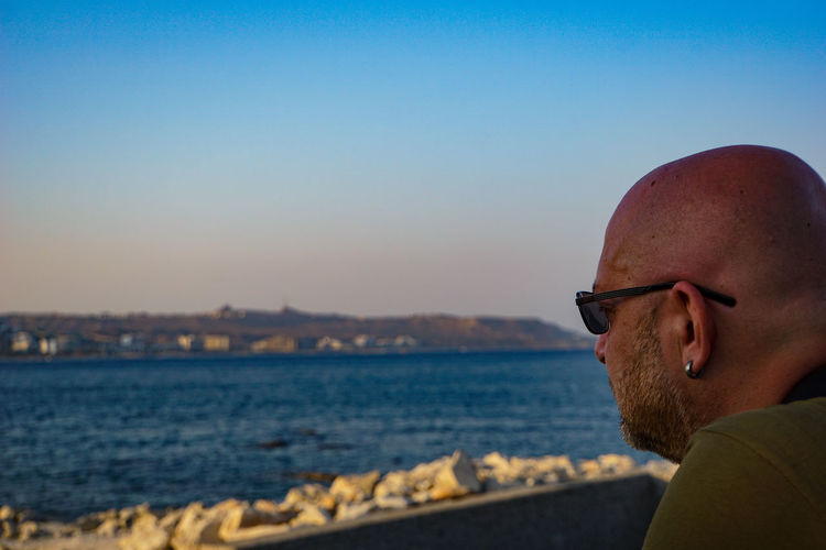 Portrait of man wearing sunglasses against clear sky