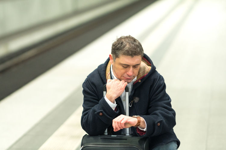 Man checking time while sitting with luggage at railroad station platform