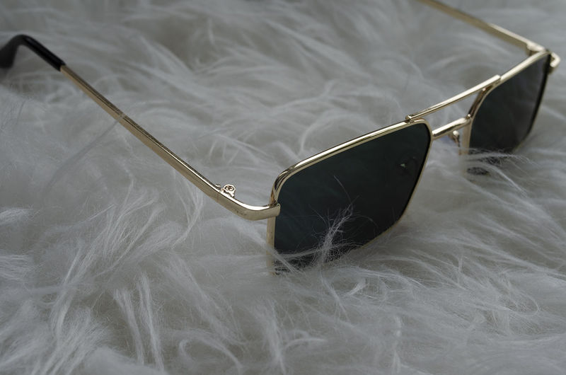 High angle view of sunglasses on bed