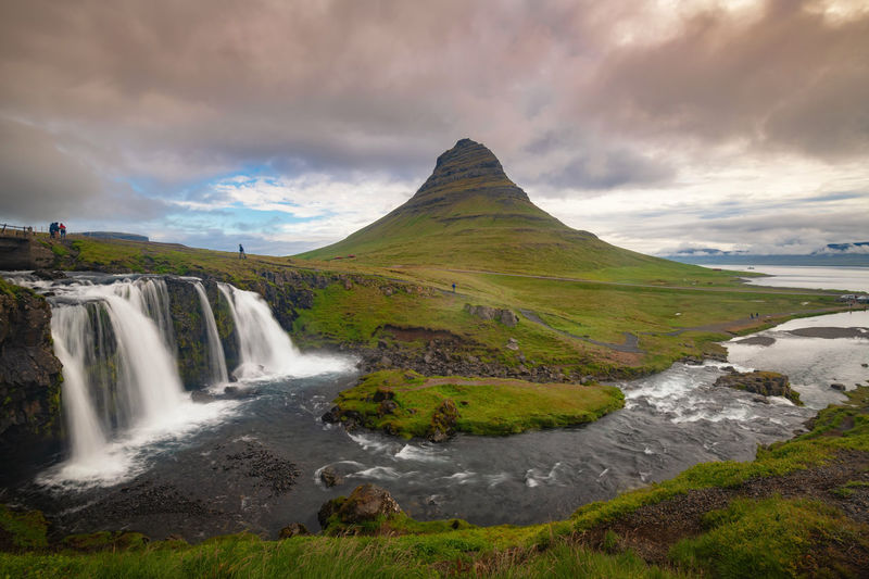 Kirkjufellfoss and Kirkjufell mountain in cloudy day ,Iceland. Iceland Kirkjufell Mountain, Nature Beauty In Nature Environment Land Landmark Landscape Long Exposure Mountain Nature Power In Nature River Scenics Scenics - Nature Sky Water Waterfall