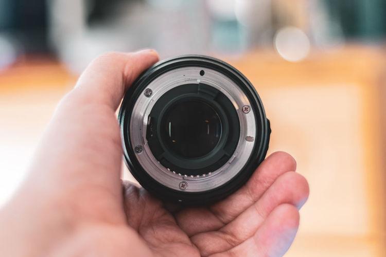 Close-up of hand holding camera lens