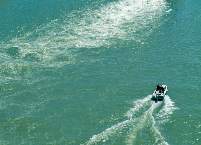 High Angle View Of Man Driving Boat In Sea
