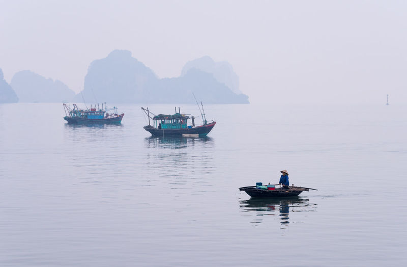 Woman on boat in sea against sky during foggy weather