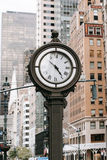 Low angle view of clock on street amidst buildings in city