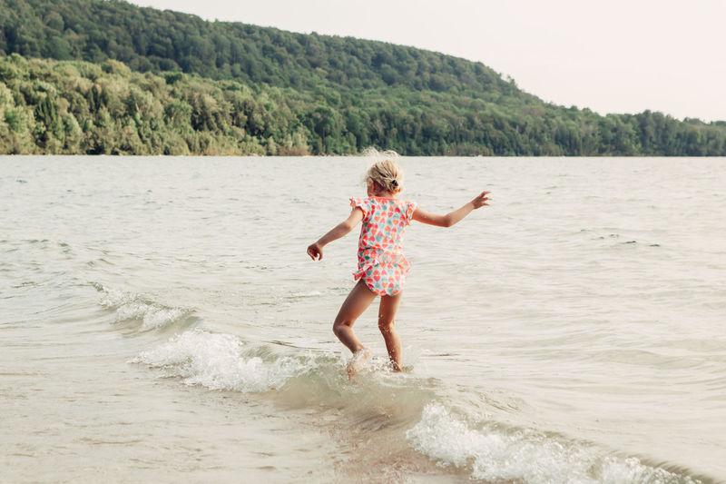 Girl enjoying at beach against cliff