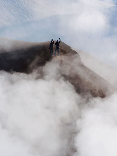 Friends standing on mountain against cloudy sky