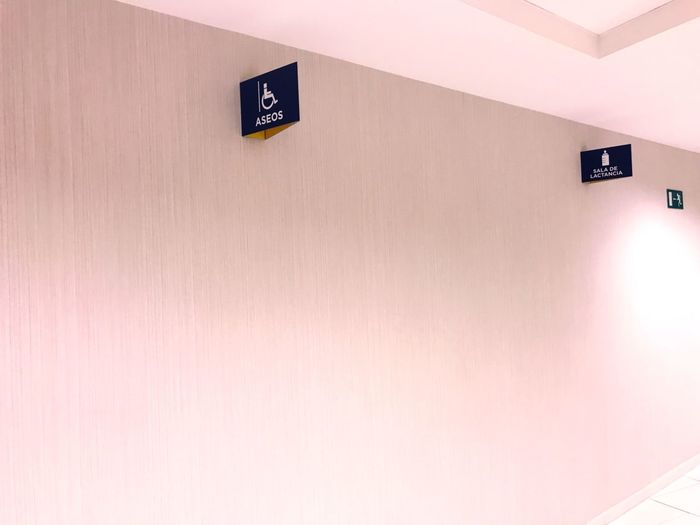 Bathroom Sign Toilette Sign Restroom Sign Wall - Building Feature Architecture No People Built Structure Indoors  Communication Sign Copy Space Wall White Color Wood - Material Information Sign Orange Color Text Representation Safety Low Angle View Information Ceiling