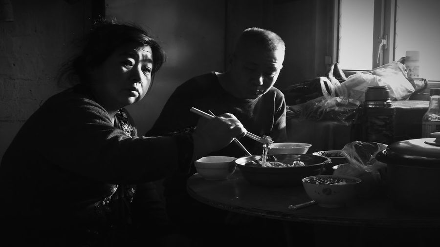 Couple having food on table at home