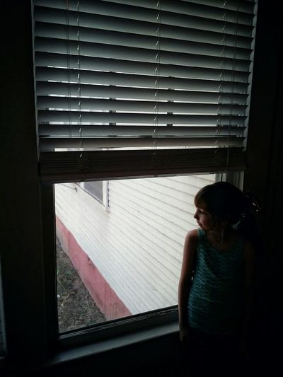 Girl Looking Illuminated Watching Light And Shadow Inside Child Window Looking Through Window Architecture Thoughtful Shutter Head And Shoulders Closed Day Dreaming Thinking Blinds Introspection Pretty