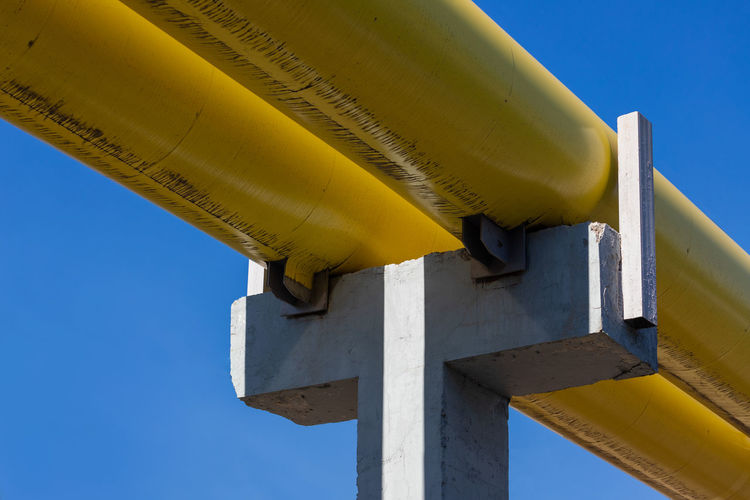 Low angle view of yellow pipe against clear blue sky