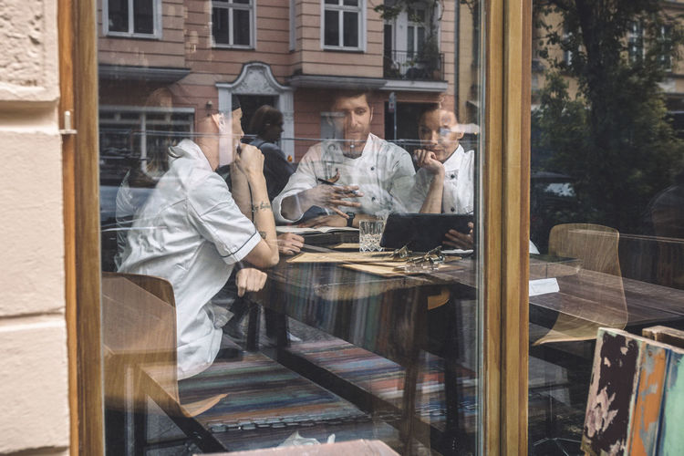 Reflection of people on glass table at restaurant