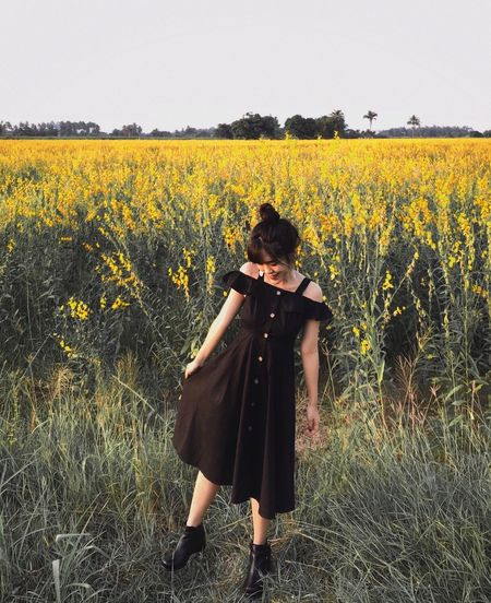 Woman standing on field with yellow flowers