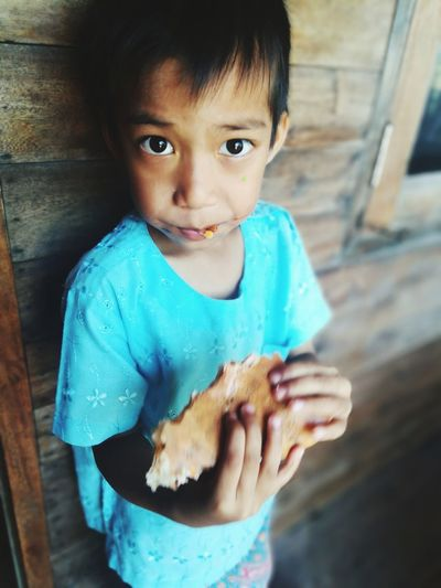 Close-up portrait of cute boy eating food while standing against wall