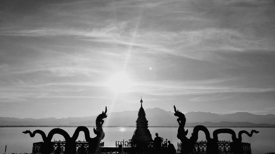 Silhouette of statue against cloudy sky