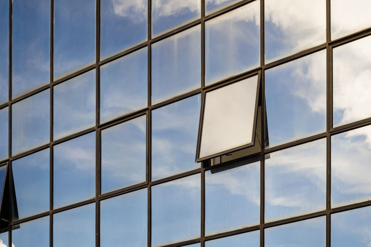 Full frame shot of glass building with reflection of sky