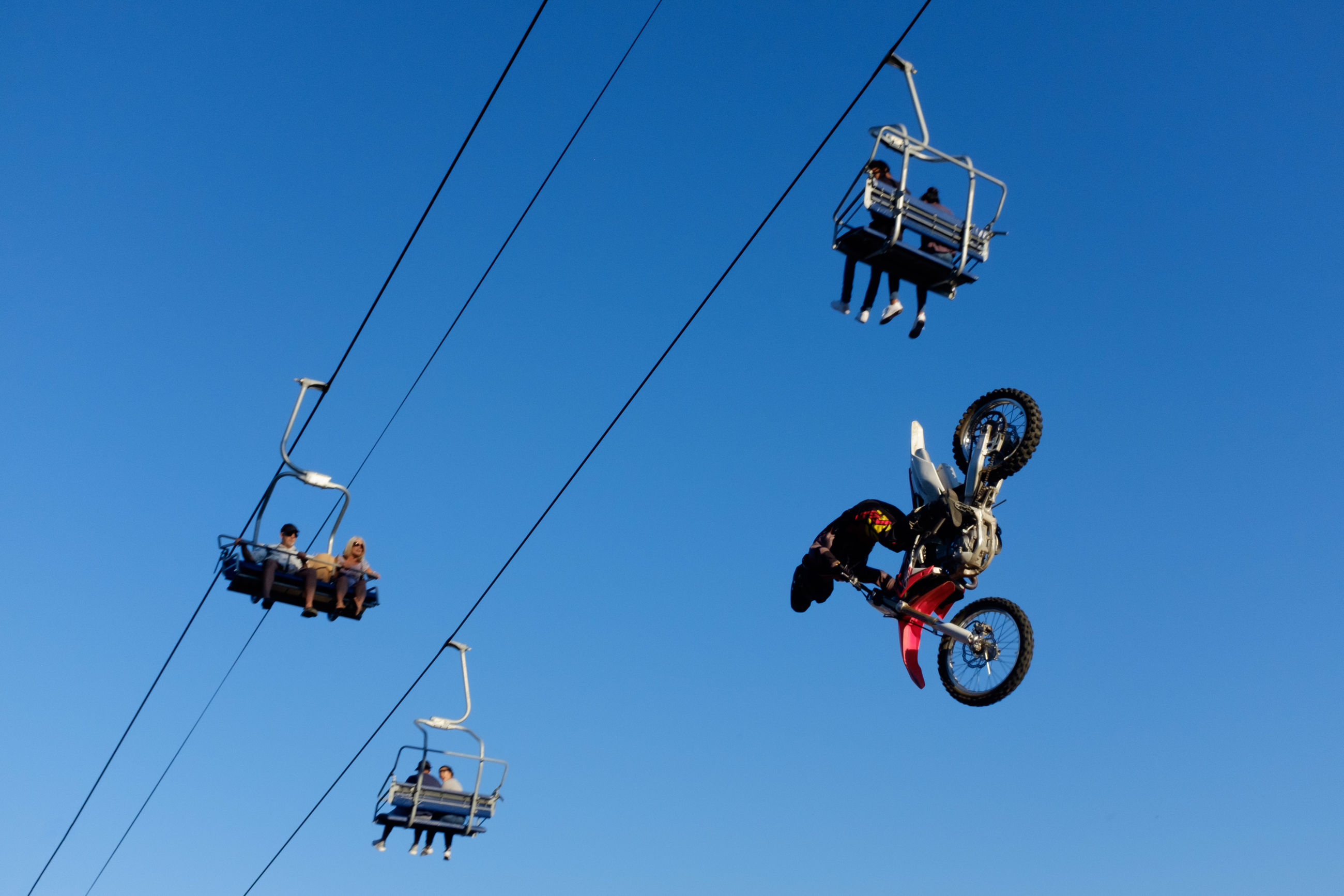 real people, adventure, extreme sports, low angle view, risk, men, leisure activity, danger, clear sky, lifestyles, mid-air, day, blue, transportation, outdoors, two people, stunt, overhead cable car, sky, stunt person, ski lift, people
