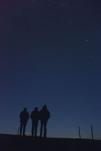 Silhouette people standing against star field at night