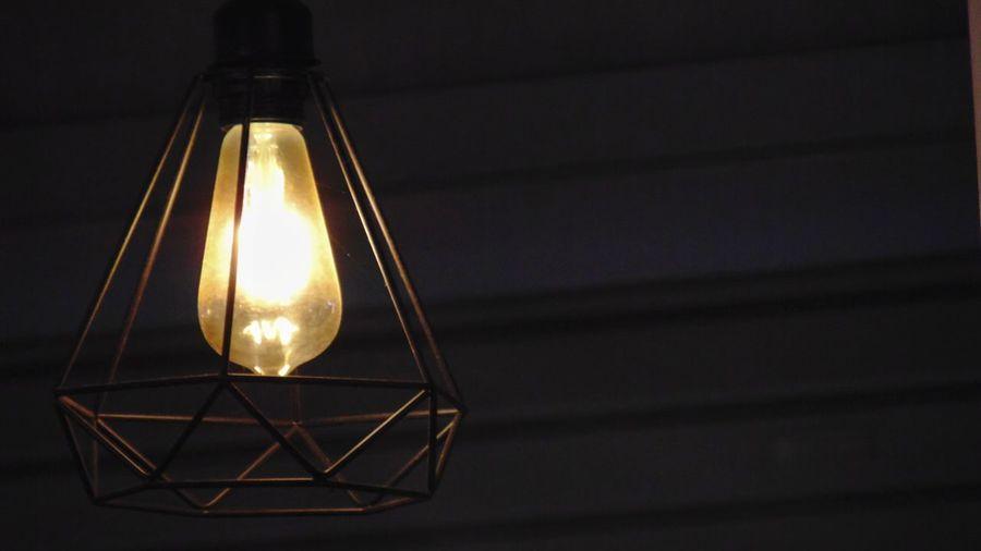 Close-up of illuminated light bulb against wall