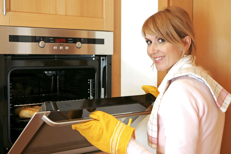 Portrait Of Smiling Woman Baking In Kitchen At Home