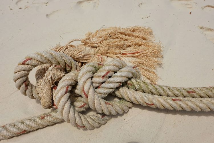 High angle view of rope tied on sandy beach