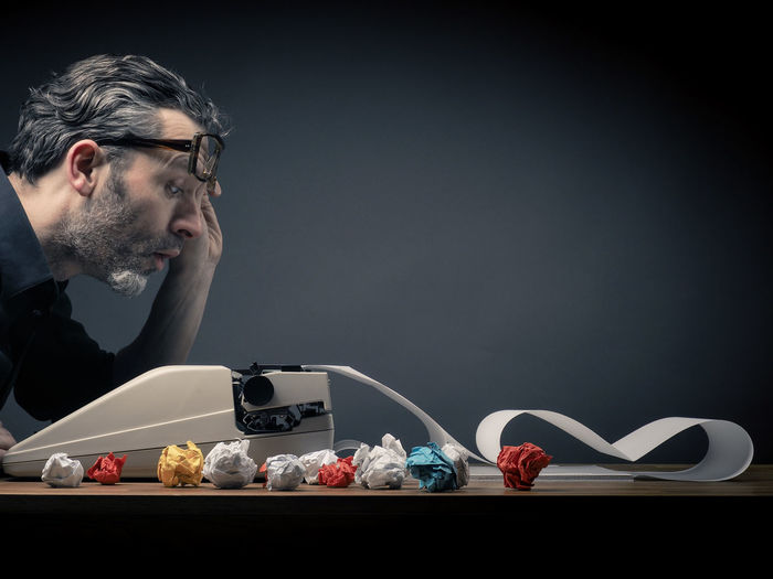Editor at work with a typewriter Creativity Letters Adult Bearded Black Background Book Close-up Creative Crumpled Paper Day Editorial  Eyeglasses  Hipster Ideas Indoors  One Person Paper Sheet People Real People Studio Shot Table Typewriter Uniqueness Young Adult