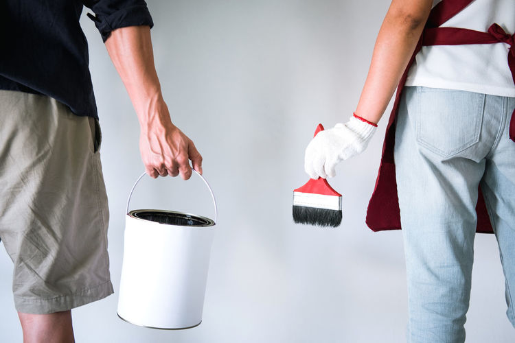 Midsection Of Friends Holding Paintbrush And Can While Standing Against White Wall