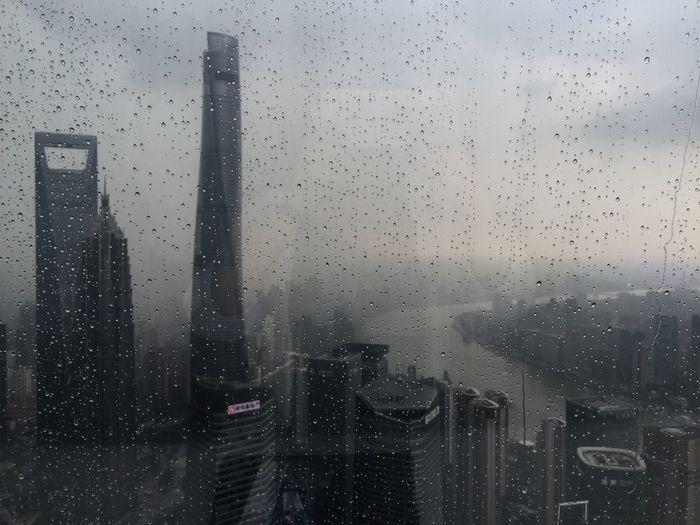 Buildings in city seen through wet window during rainy season