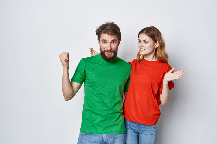 Portrait of young couple standing against white background