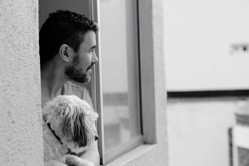 Man with dog looking through window