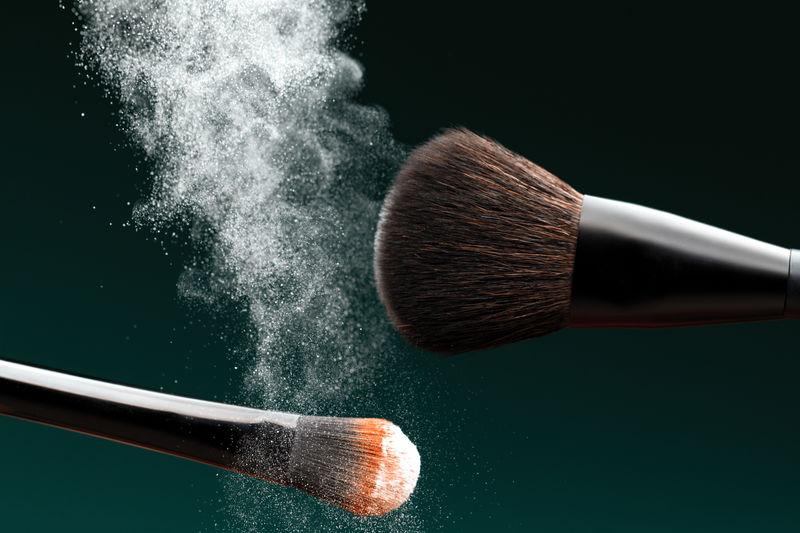 Close-up of make-up brushes against black background