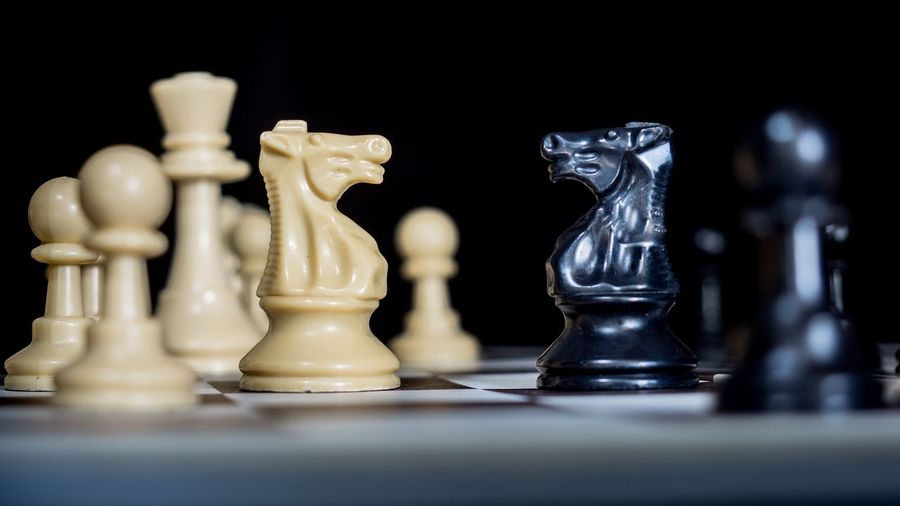 Close-up of chess board on table against black background