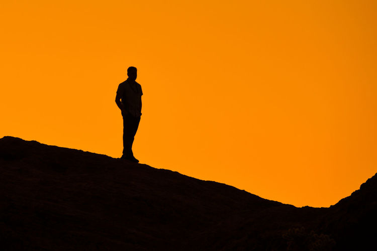 Silhouette man standing on field against clear orange sky